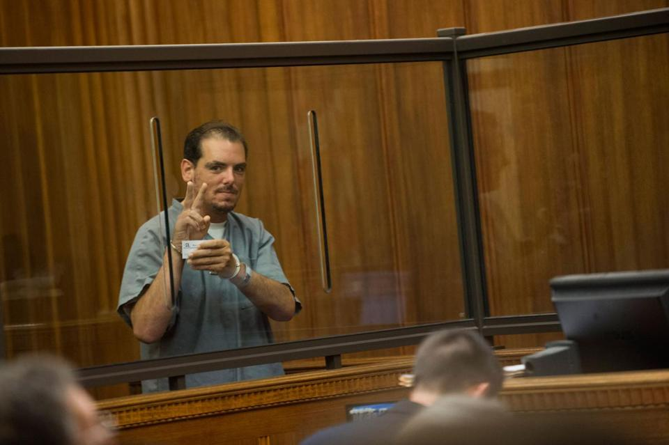 Michael Bourne gave the peace sign to his family during an arraignment in Dedham.